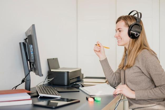 Smiley femme au bureau portant des écouteurs et ayant un cours en ligne