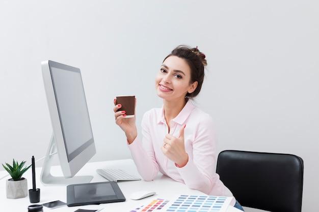 Smiley femme au bureau tenant une tasse de café et donner les pouces vers le haut