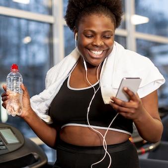 Smiley femme au gymnase à l'aide de mobile