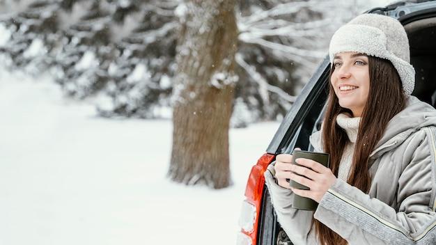 Smiley femme ayant une boisson chaude lors d'un voyage sur la route avec copie espace