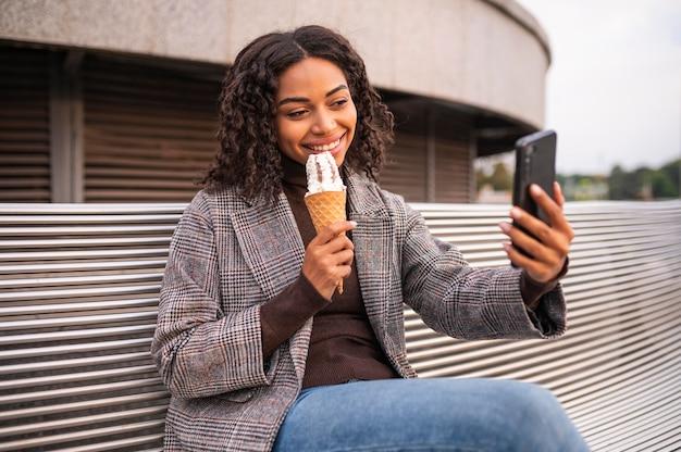 Smiley femme ayant de la crème glacée à l'extérieur et prenant selfie