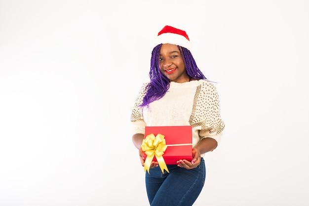 Smiley femme avec bonnet de noel tenant le cadeau de noël