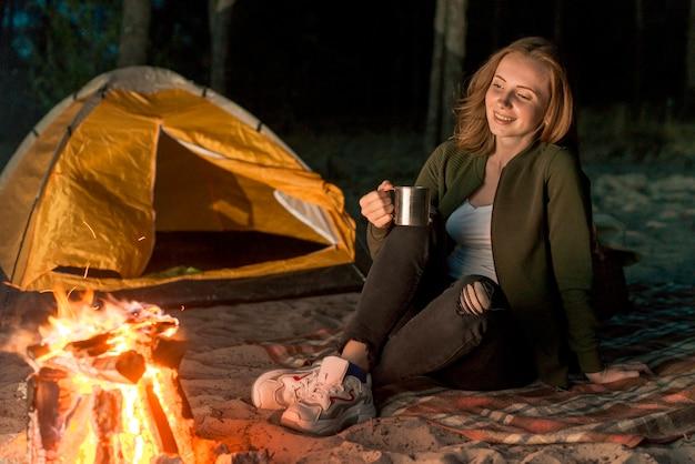 Smiley femme buvant devant un feu de camp