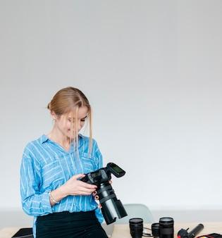 Smiley femme en chemise bleue tenant un appareil photo et regardant vers le bas