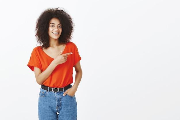Smiley femme avec une coiffure afro qui pose en studio