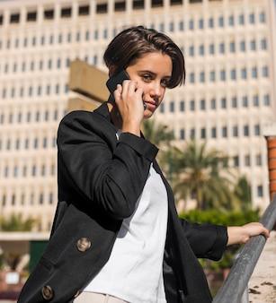Smiley femme élégante parlant au téléphone