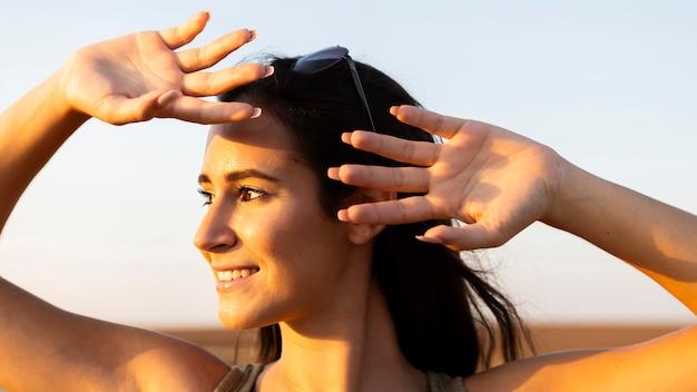 Smiley femme à l'extérieur au soleil couvrant son visage