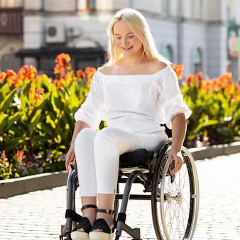 Smiley femme en fauteuil roulant dans la ville