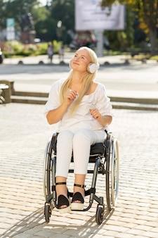 Smiley femme en fauteuil roulant, écouter de la musique sur des écouteurs à l'extérieur