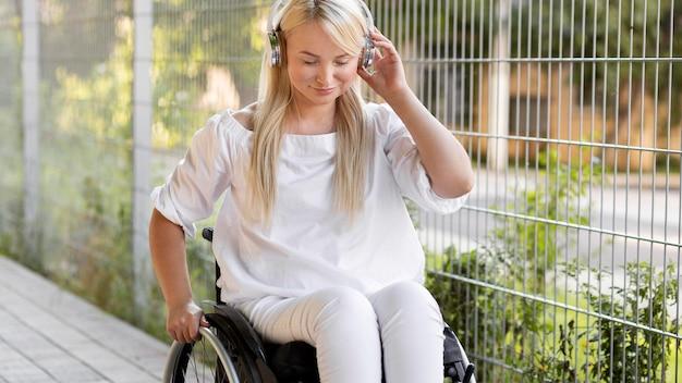 Smiley femme en fauteuil roulant avec des écouteurs à l'extérieur