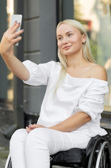 Smiley femme en fauteuil roulant prenant selfie avec smartphone