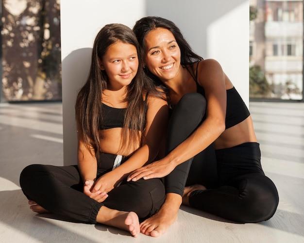 Smiley femme et fille assise ensemble