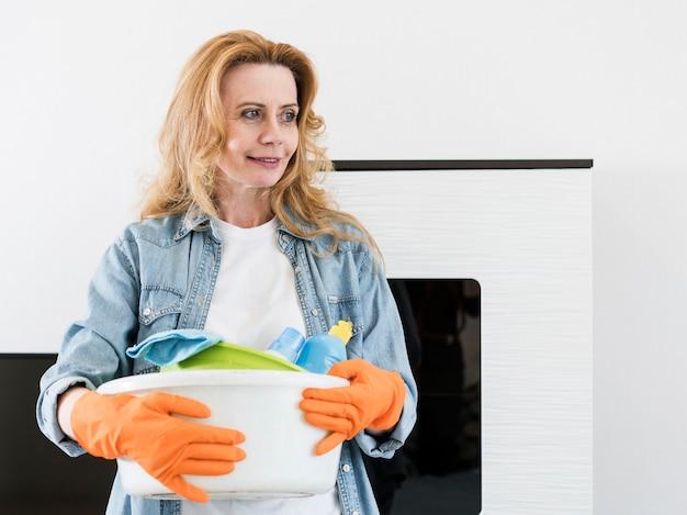 Smiley femme avec des gants en caoutchouc tenant le panier de produits de nettoyage