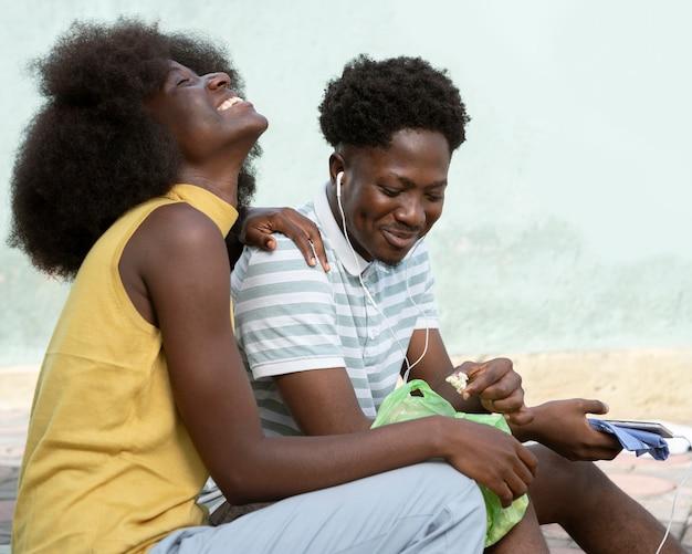 Smiley femme et homme écoutant de la musique