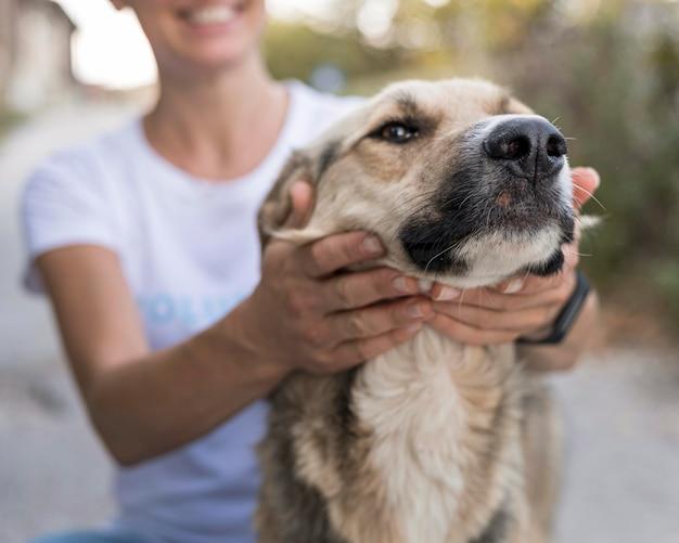 Smiley femme jouant avec un chien mignon à l'extérieur