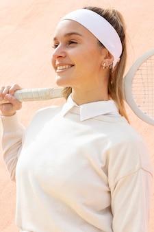 Smiley femme joueuse de tennis à la recherche de suite