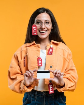 Smiley femme avec des lunettes tenant une carte de crédit tout en étant couvert d'étiquettes de vente