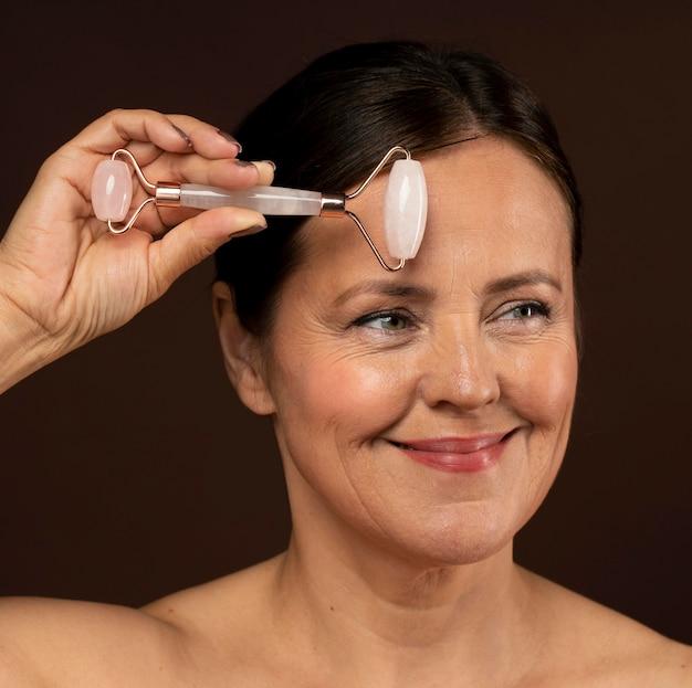 Smiley femme mature à l'aide d'un rouleau de quartz rose sur son visage