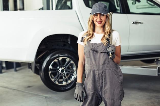 Smiley femme mécanicien tenant une clé