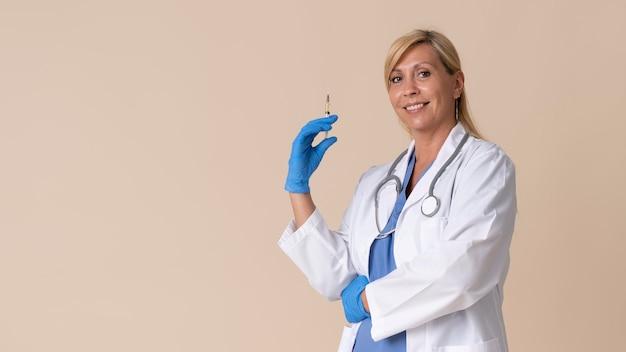 Smiley femme médecin tenant une seringue de vaccin