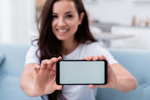 Smiley femme montrant son téléphone d'affichage vide