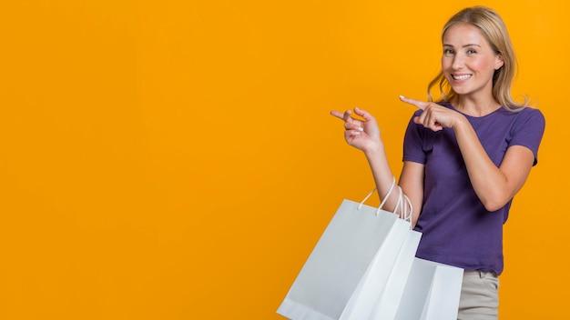 Smiley femme avec de nombreux sacs à provisions pointant sur magasin possible avec espace copie