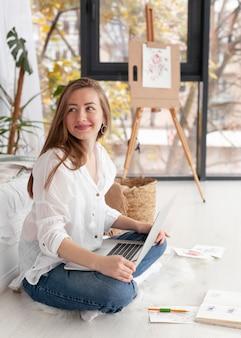Smiley femme avec ordinateur portable sur ses genoux