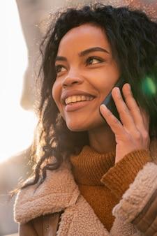Smiley femme parlant au téléphone à l'extérieur