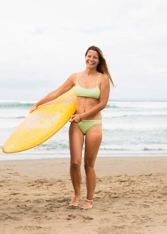 Smiley femme sur la plage tenant planche de surf