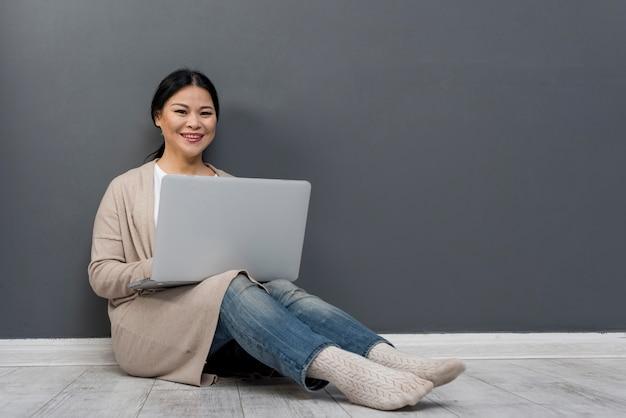 Smiley femme sur plancher avec ordinateur portable