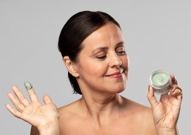 Smiley femme plus âgée à l'aide d'un masque facial