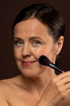 Smiley femme plus âgée à l'aide d'un pinceau de maquillage sur son visage
