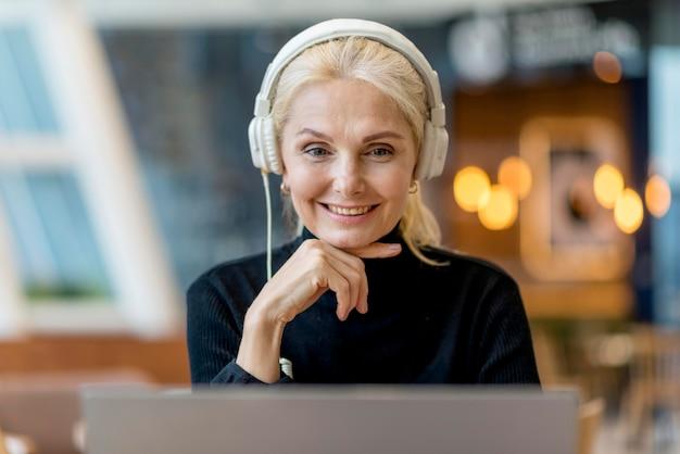 Smiley femme plus âgée lors d'une conférence avec des écouteurs