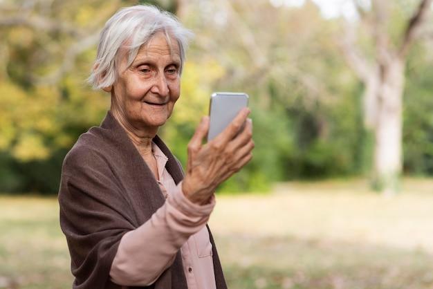 Smiley femme plus âgée tenant le smartphone à l'extérieur