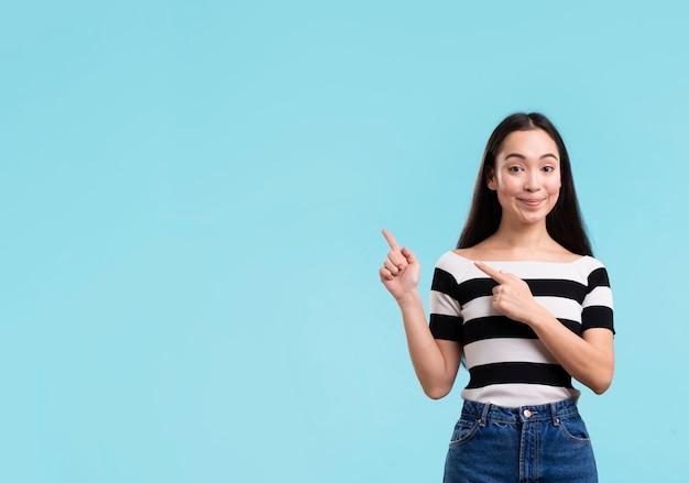 Smiley femme pointant avec copie-espace