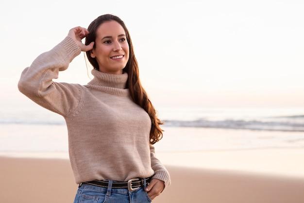 Smiley femme posant au bord de la plage au coucher du soleil