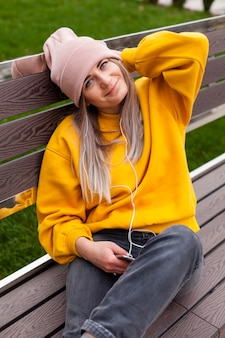 Smiley femme posant sur un banc tout en portant un bonnet