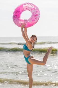 Smiley femme posant avec bouée de sauvetage