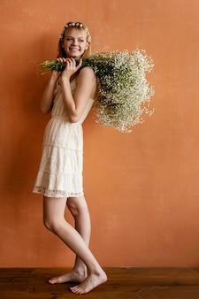 Smiley femme posant avec bouquet de fleurs