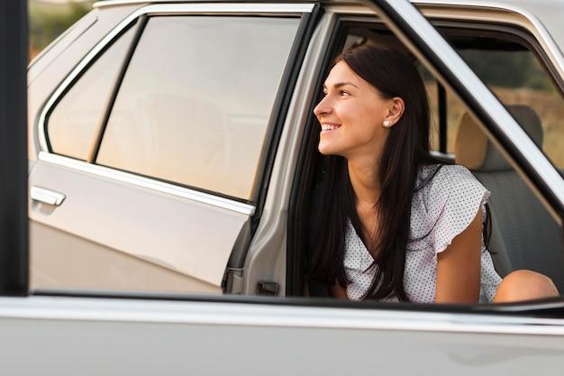 Smiley femme posant dans la voiture