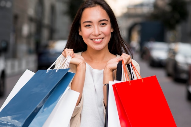 Smiley femme posant avec des sacs après l'achat de vente
