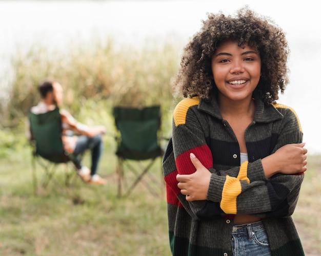 Smiley femme posant tandis que petit ami se détendre sur une chaise à l'extérieur