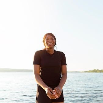 Smiley femme posant tout en exerçant au bord du lac