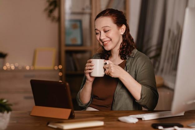 Smiley femme prenant un café à la maison et à l'aide de sa tablette