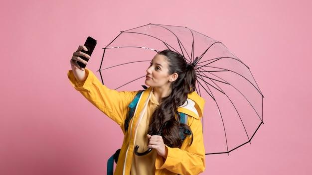Smiley femme prenant un selfie tout en tenant un parapluie