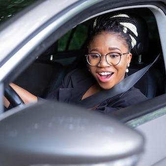 Smiley femme regardant dans son miroir de voiture