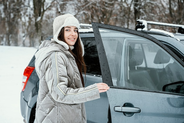 Smiley femme rentrer dans la voiture lors d'un road trip