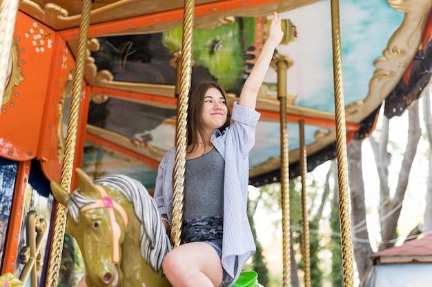Smiley femme s'amusant dans le carrousel