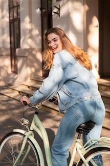 Smiley femme s'amusant à faire du vélo dans la ville