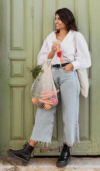 Smiley femme avec des sacs d'épicerie ayant de la soude à l'extérieur